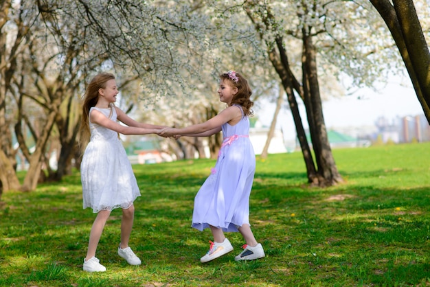 Mooie jonge meisjes met blauwe ogen in een witte jurk in de tuin met bloeiende appelbomen plezier maken en genieten van de geur van bloeiende lentetuin.