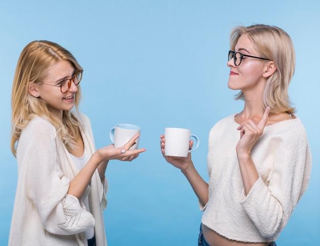 Mooie jonge meisjes met koffiemokken