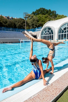Mooie jonge meisjes poseren bij het zwembad