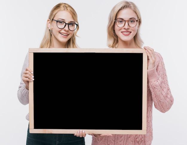 Mooie jonge meisjes samen met mock-up