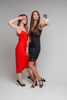 Mooie jonge meisjesbloggers die stijlvolle jurken dragen, maken selfie-fotografie met behulp van de telefoon die zich voordeed op een grijze muur