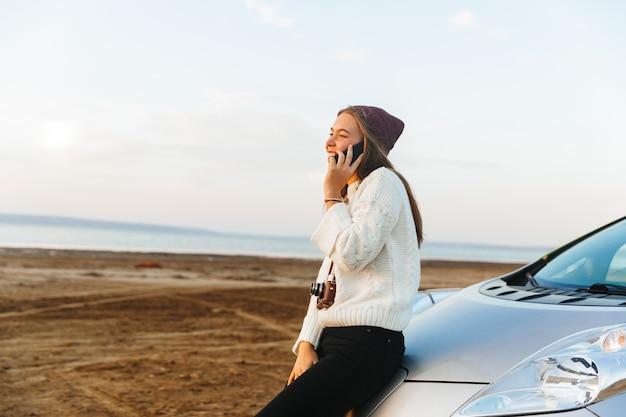 Mooie jonge meisjestoerist die bij haar auto zit, die op zonsondergang kijkt, die op mobiele telefoon spreekt