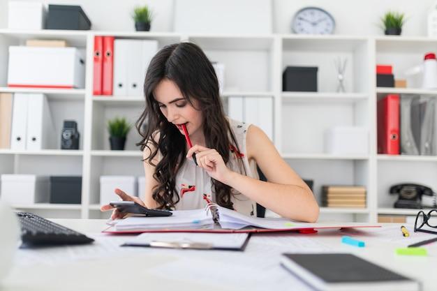 Mooie jonge meisjeszitting bij een bureau dat een pen in haar mond houdt en de calculator onderzoekt.