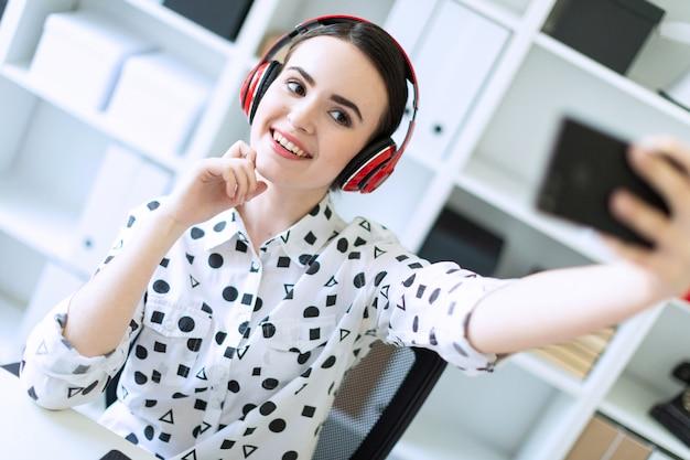 Mooie jonge meisjeszitting in hoofdtelefoons bij bureau in bureau en het nemen van beelden van zich op de telefoon.