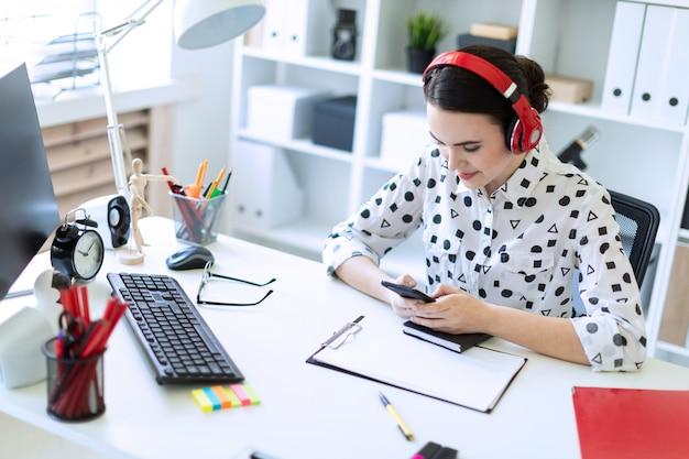 Mooie jonge meisjeszitting in hoofdtelefoons bij bureau in bureau en holding een telefoon.