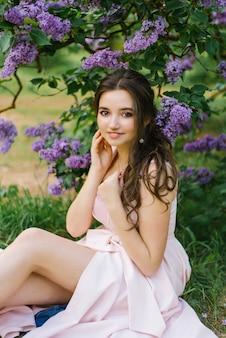 Mooie jonge meisjeszitting op de grond in de tuin met bloeiende sering. ze is gelukkig en geniet van haar jeugd en lente. professionele make-up en schone mooie huid