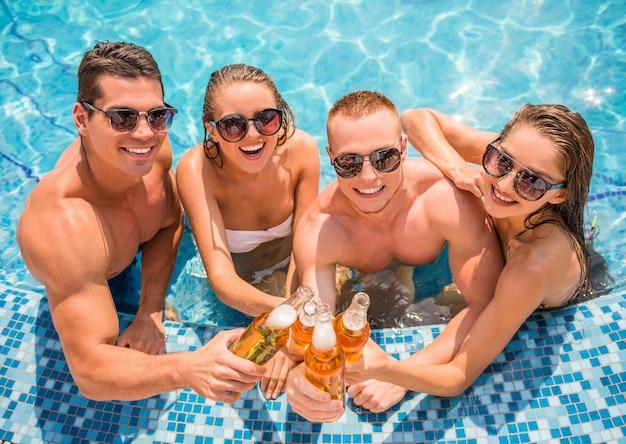 Mooie jonge mensen die plezier hebben in het zwembad.
