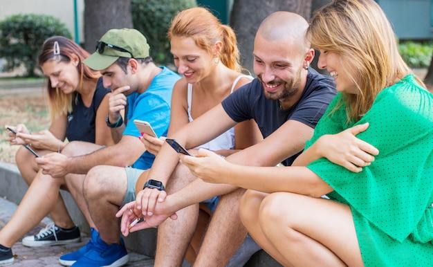 Mooie jonge mensen gebruiken smartphones en glimlachen terwijl ze buiten zitten