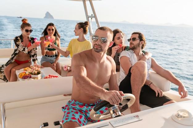 Mooie jonge mensen ontspannen op een luxe jacht. ze zitten aan tafel, drinken cocktails en eten tropisch fruit. focus op de knappe kapitein met ontbloot bovenlijf die het jacht bestuurt.