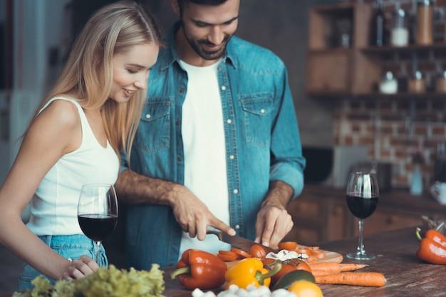Mooie jonge mensen praten en glimlachen tijdens het koken van gezond voedsel in de keuken thuis