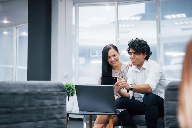 Mooie jonge mensen. selfie van twee glimlachende beambten in officiële kleding die dichtbij zilveren laptop op lijst zitten