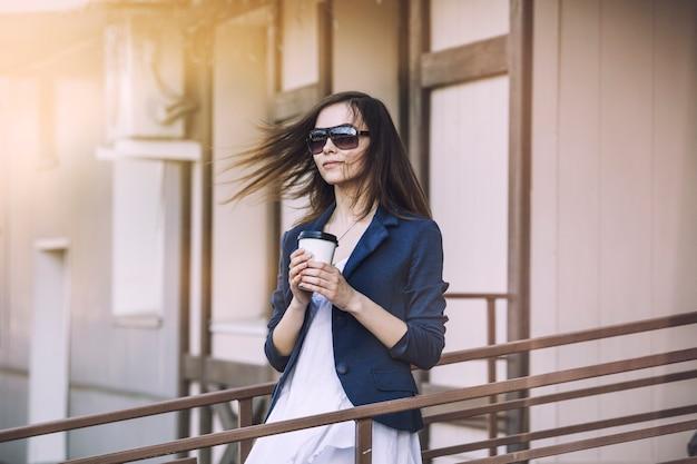 Mooie jonge mode meisje komt uit een café met afhaalkoffie in de hand