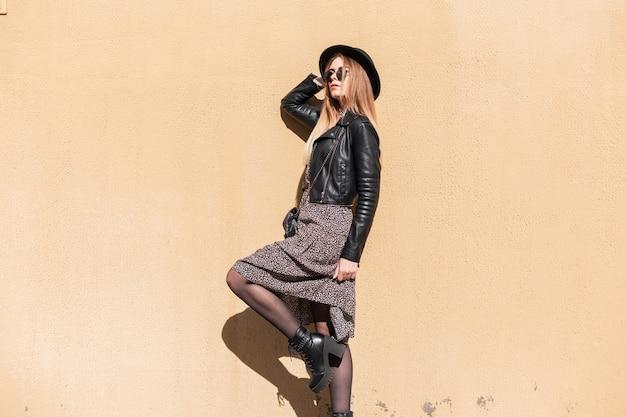 Mooie jonge mode sensuele vrouw gekleed in hipster stijl kleding outfit met jas, jurk, zonnebril, hoed en schoenen poses in de buurt van een muur.