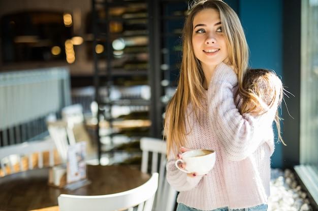Mooie jonge model student tiener gekleed in casual kleding jeans in café houdt koffie thee beker in haar handen