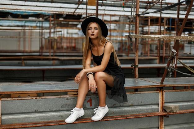 Mooie jonge model vrouw in modieuze zwarte hoed en zwarte rok met witte sneakers zit op een metalen oppervlak