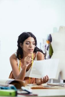 Mooie jonge modeontwerper kijkt naar geprint moodboard bij het werken aan nieuwe collectie voor upcom...