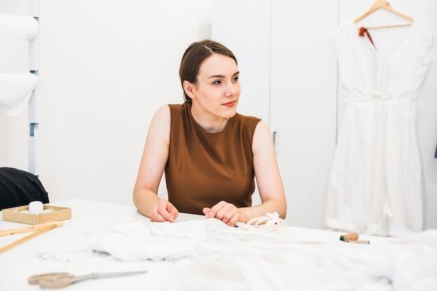 Mooie jonge modeontwerper met jurk op de werktafel