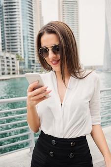 Mooie jonge moderne zakenvrouw permanent in een dubai marine en kijken naar haar telefoon.