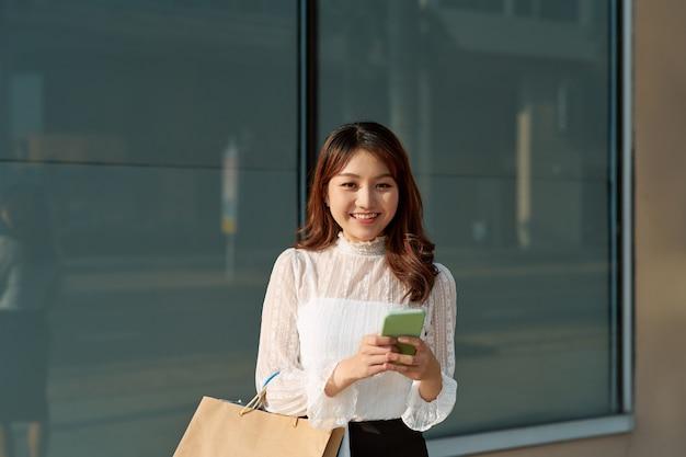 Mooie jonge modevrouw met boodschappentassen in de buurt van etalage die smartphone belt