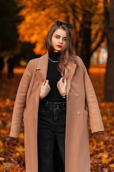 Mooie jonge modieuze vrouw in een stijlvolle beige jas en trui loopt in een herfstpark met gekleurd oranje blad