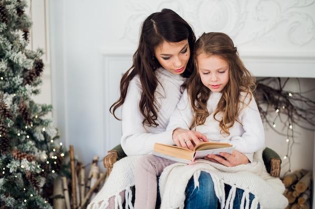 Mooie jonge moeder die een boek leest aan haar schattige dochter in de buurt van boom binnenshuis