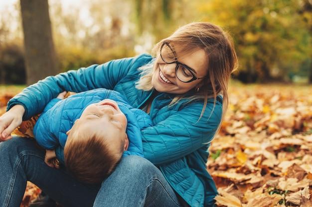 Mooie jonge moeder die een bril draagt die op de grond zit, zijn zoontje op de benen houdt en met hem speelt lachen. varken