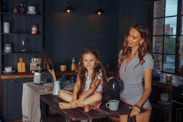 Mooie jonge moeder die en pret met haar kleine leuke dochter in een donker keukenbinnenland thuis speelt heeft