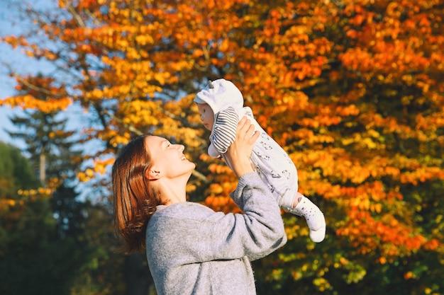 Mooie jonge moeder die haar baby in de armen houdt in het herfstpark. gelukkige moeder met haar kind op de natuur.