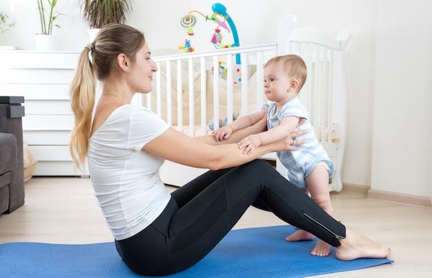 Mooie jonge moeder die zich uitstrekt op fitnessmat met haar babyjongen