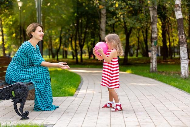 Mooie jonge moeder en dochter in warme zonnige zomerdag. gelukkig gezin moeder en kind dochtertje spelen met een ballon en wandelen in het park en genieten van de prachtige natuur.