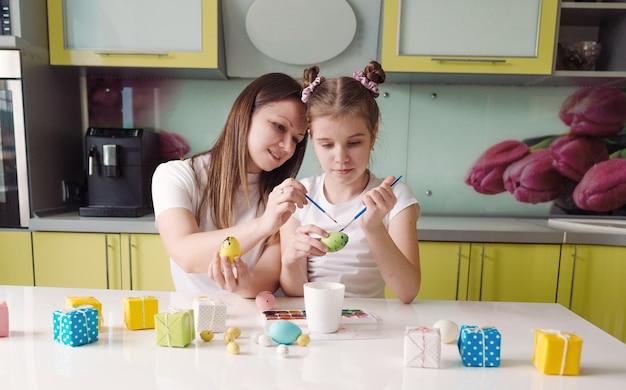 Mooie jonge moeder en dochter schilderen thuis paaseieren in de keuken. voorbereiden op de paasvakantie