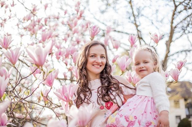 Mooie jonge moeder en dochtertje in de buurt van een bloeiende magnolia. voorjaar. roze bloemen.