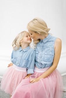 Mooie jonge moeder en haar dochter die dezelfde kleren