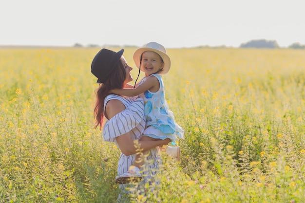 Mooie jonge moeder en haar dochter die pret hebben bij het tarweveld.