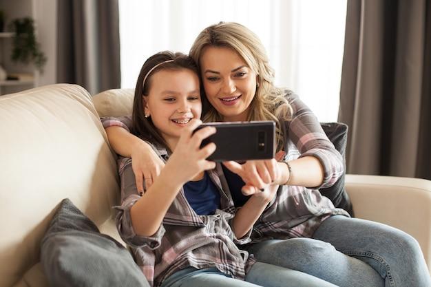 Mooie jonge moeder en haar dochter gebruiken een smartphone en glimlachen zittend op de bank in de woonkamer.