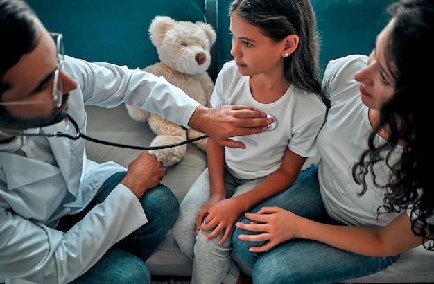 Mooie jonge moeder en haar dochtertje thuis. arts onderzoekt kleine patiënt met behulp van een stethoscoop