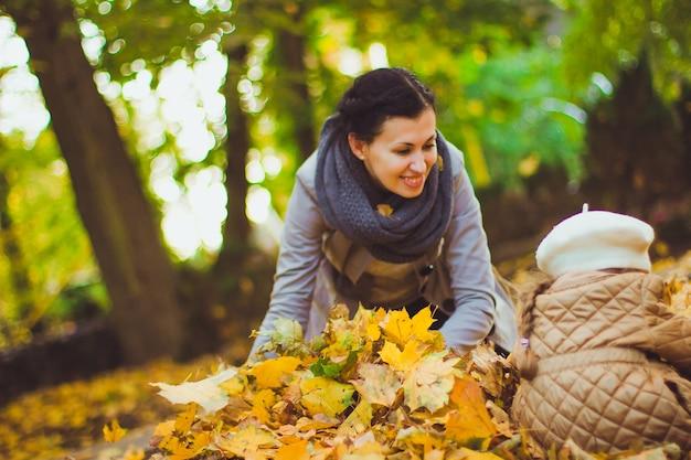 Mooie jonge moeder en haar gelukkige dochter hebben plezier in het bos in de herfst. wandelingen in een herfstpark met de kinderen. familie besteedt veel tijd aan het spelen samen met gevallen bladeren.