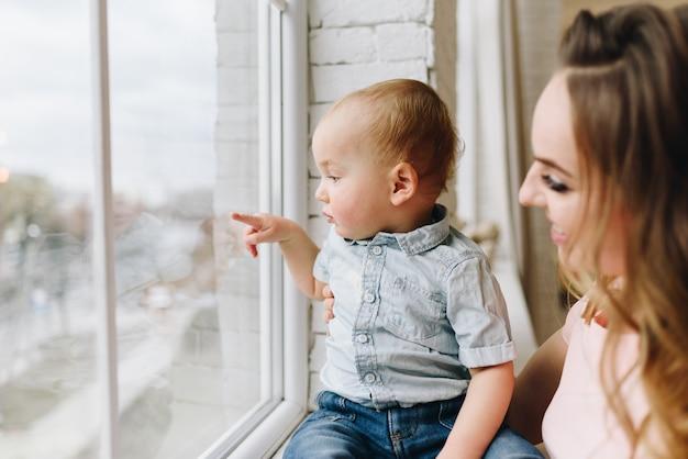 Mooie jonge moeder en haar kleine zoon kijken uit het raam