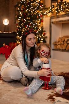 Mooie jonge moeder en leuk dochtermeisje in modieuze pyjama's zitten en spelen met speelgoed bij de open haard met kerstversiering en verlichting