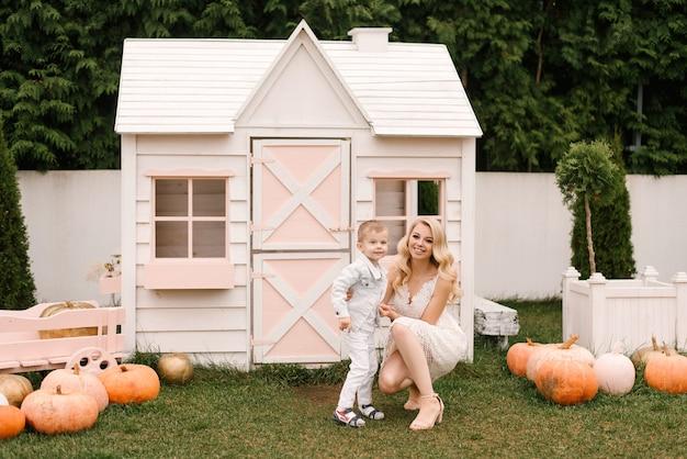 Mooie jonge moeder en zoon knuffelen en spelen thuis in slimme kleding