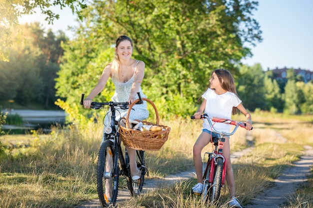 Mooie jonge moeder fietsen met dochter rijden naar picknick