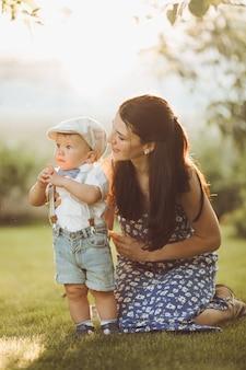 Mooie jonge moeder gaat wandelen met haar kleine blanke baby in het park