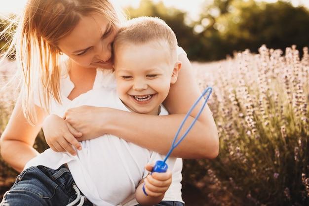 Mooie jonge moeder haar zoon buiten kietelen. mooie jonge vrouw speelt met haar zoontje buiten tegen zonsondergang in een veld met bloemen.