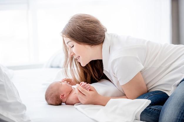 Mooie jonge moeder hand in hand van haar slapende pasgeboren baby dochter in het bed en kijken naar haar met een glimlach. ouder en kind kind. gelukkige momenten van wiskunde