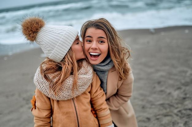 Mooie jonge moeder in een jas heeft plezier met haar schattige dochter die in de winter haar moeder op de wang kust.