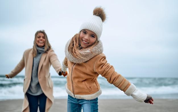 Mooie jonge moeder in een jas heeft plezier met haar schattige dochter op het strand in de winter.