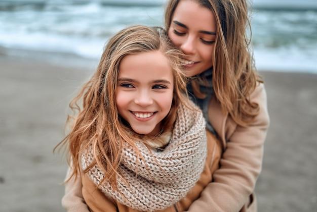 Mooie jonge moeder in een jas met haar schattige mooie dochter op het strand in de winter.