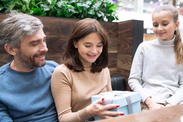 Mooie jonge moeder kijken naar geschenkdoos in haar handen omringd door man en dochter terwijl ze tijd doorbrengen in café