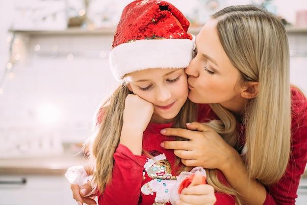 Mooie jonge moeder kust haar tienerdochter op de wang in de keuken