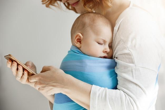 Mooie jonge moeder leest artikelen over het moederschapsleven op de telefoon terwijl kleine mooie zoon slaapt op haar borst in blauwe draagdoek.